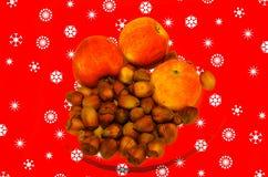 的苹果在圣诞节背景的榛子 图库摄影