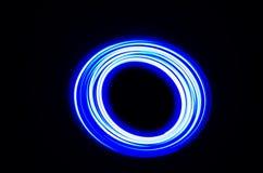 轻的螺旋和蓝线在黑背景 库存照片