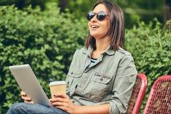 的行家妇女有咖啡和片剂计算机的太阳镜 免版税图库摄影