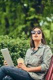 的行家妇女有咖啡和片剂计算机的太阳镜 库存图片