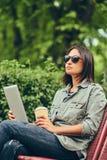 的行家妇女有咖啡和片剂计算机的太阳镜 图库摄影