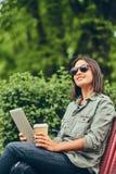 的行家妇女有咖啡和片剂计算机的太阳镜 免版税库存照片
