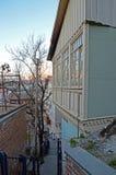 的被雕刻的木阳台在日落的狭窄的街道台阶 老第比利斯,乔治亚 免版税图库摄影
