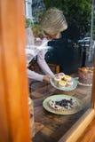 的资深妇女拿着在板材的大角度观点杯形蛋糕 库存照片