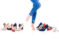 的赤足女孩站立在被停顿的鞋子附近的播种的观点,隔绝在白色 库存图片