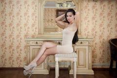 紧的适合短小裸体礼服的迷人的年轻深色的妇女在镜子前面 在镜子附近的性感的华美的长的头发女孩 免版税图库摄影