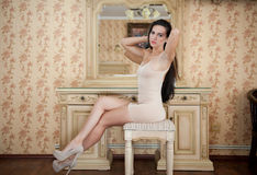 紧的适合短小裸体礼服的迷人的年轻深色的妇女在镜子前面 在镜子附近的性感的华美的长的头发女孩 免版税库存照片
