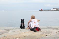 的里雅斯特, 2017年9月5日,意大利:一名妇女坐有两条狗的一个石码头 库存照片