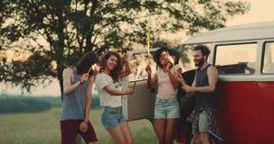 的野餐和的藏品的跳舞朋友闪烁发光物在愉快的手上享受时间,在他们的葡萄酒搬运车旁边 股票录像