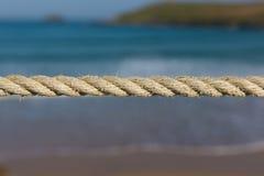 绳索的长度紧紧拉扯了反对海波浪和海岸被弄脏的背景  库存图片