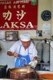 他们的阿萨姆邦Laksa面条摊位的叫卖小贩供营商在空气Itam,笔 库存图片