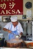 他们的阿萨姆邦Laksa面条摊位的叫卖小贩供营商在空气Itam,笔 免版税库存图片