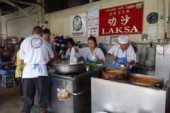 他们的阿萨姆邦Laksa面条摊位的叫卖小贩供营商在空气Itam,笔 免版税库存照片