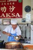 他们的阿萨姆邦Laksa面条摊位的叫卖小贩供营商在空气Itam,笔 图库摄影