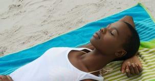 的非裔美国人的妇女睡觉在海滩4k的大角度观点 股票视频