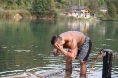 洗他的面孔的可爱的人在河 库存照片