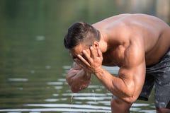 洗他的面孔的可爱的人在河 库存图片