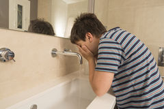 洗他的面孔的年轻男孩 免版税图库摄影