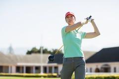 的高尔夫球运动员妇女采取射击的低角度观点 库存照片