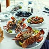 的龙虾和的菜在典型的希腊taverna,哥斯达黎加的桌 免版税库存图片