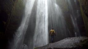 的年轻人站立在石头的后面观点在强有力的瀑布Gljufrabui附近在冰岛在大风天 影视素材