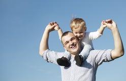 给他的年轻儿子肩扛乘驾的爸爸 免版税库存图片