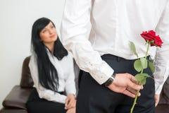 的年轻商人掩藏花的后面观点 免版税库存图片