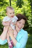 的婴孩和获得她的母亲乐趣 免版税库存照片