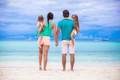的年轻家庭看对海的后面观点  免版税库存照片