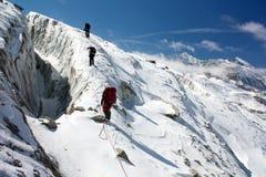 组绳索的登山人在冰川 图库摄影