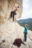 去的登山人截去绳索在路线开始  免版税库存图片