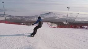 的年轻挡雪板迅速滑下来在倾斜的后面观点在高山的滑雪胜地在晴天 人 股票录像