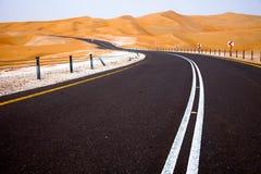 绞的黑柏油路通过Liwa绿洲,阿联酋沙丘  免版税库存图片