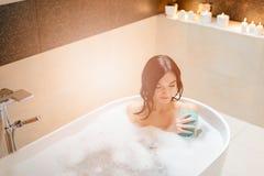 洗浴的年轻深色的妇女 库存照片