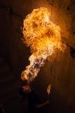 年轻从他的嘴的人吹的火 库存照片