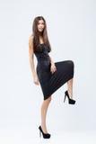 紧的黑礼服的美丽,大踏步走的女孩,隔绝在白色 库存照片