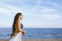 的画象有享受海风景的性感的身体的年轻梦想的妇女的,当晒日光浴在海滩时 免版税库存照片