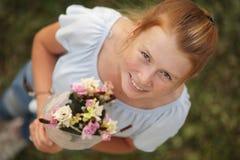 的redhair女孩拿着花花束和微笑对照相机的顶上的观点 库存图片