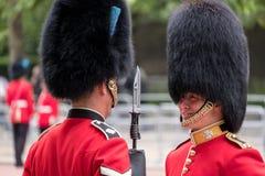 皇家卫兵战士有一次亲密的交谈在进军期间颜色军事仪式,每年一次举行在伦敦 库存照片