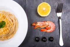 皇家大虾用柠檬和橄榄在板材旁边有意粉的 在视图之上 免版税库存图片