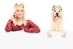 皇家女性和狗佩带的冠和摆在面板之后 免版税库存图片