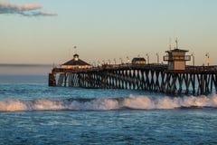 皇家海滩渔码头在与碰撞的波浪的黎明 免版税库存图片