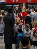 皇家骑马卫兵的战士在伦敦,围拢由游人包括在前景的犹太家庭 图库摄影