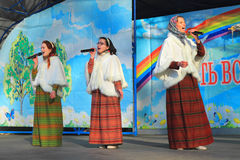 皇家Maslenitsa -全国衣服的三名妇女在场面唱歌 图库摄影