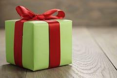绿皮书有经典红色丝带弓的礼物盒在木桌上 库存照片