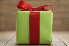 绿皮书有经典红色丝带弓的礼物盒在木桌上 免版税库存图片
