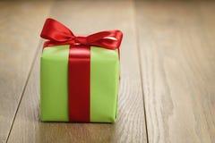 绿皮书有经典红色丝带弓的礼物盒在木桌上 免版税库存照片