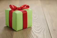 绿皮书有经典红色丝带弓的礼物盒在木桌上 库存图片
