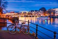 皮包骨头的桥梁和Amstel河在黄昏的阿姆斯特丹荷兰 免版税库存照片
