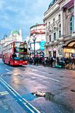 皮卡迪利广场霓虹标志在有公共汽车的街道上反射了 免版税库存照片